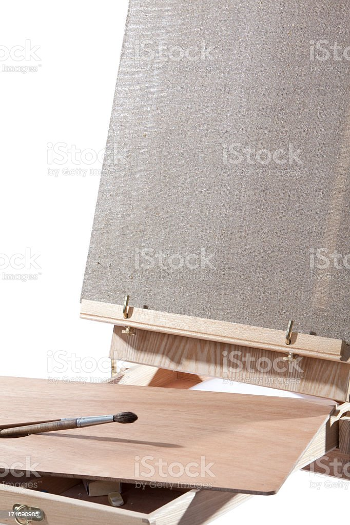 Wooden easel with blank canvas and paint brush stock photo