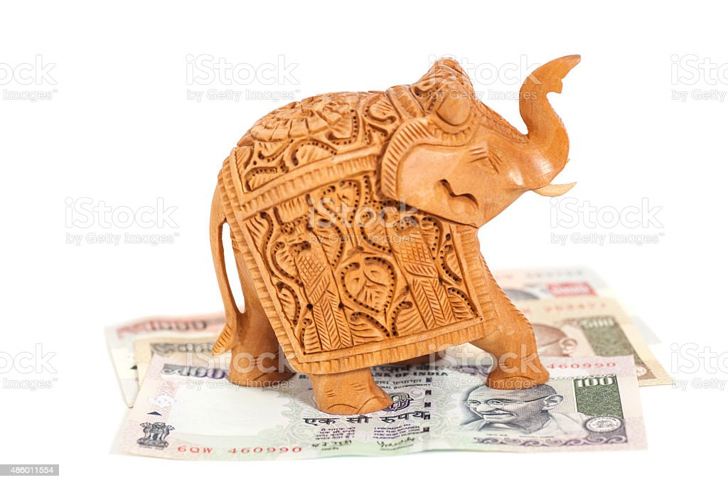 Wooden elephant sculpture on Indian  Rupee banknotes stock photo