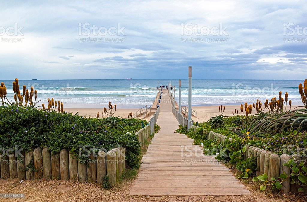 Wooden Entrance onto Pier Lined with Orange Aloes stock photo