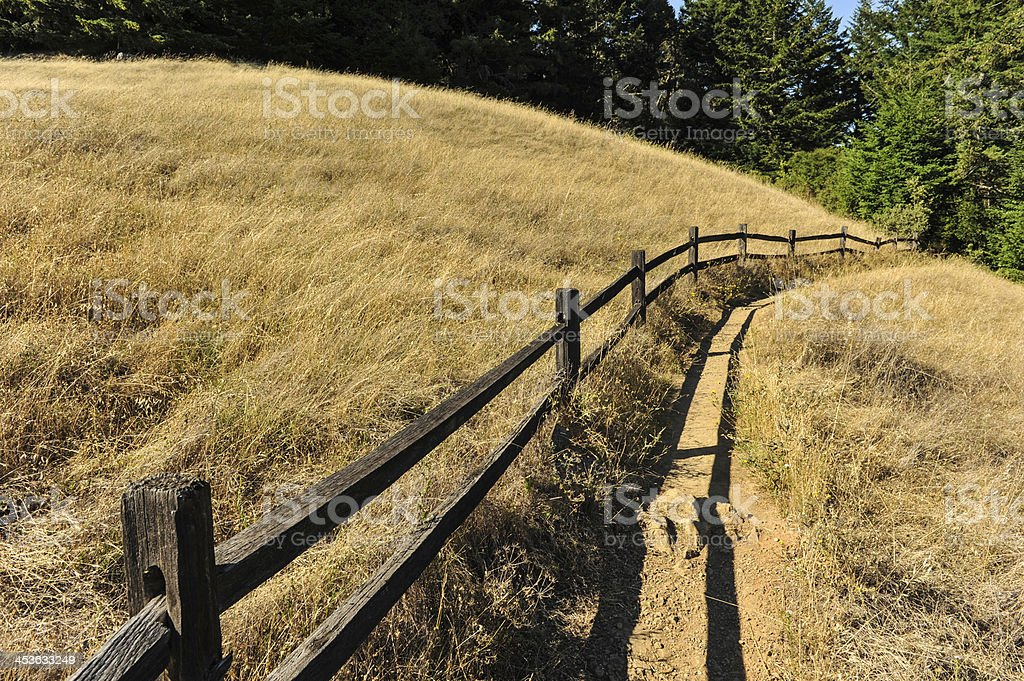 Wooden fence along a hiking trail near field royalty-free stock photo