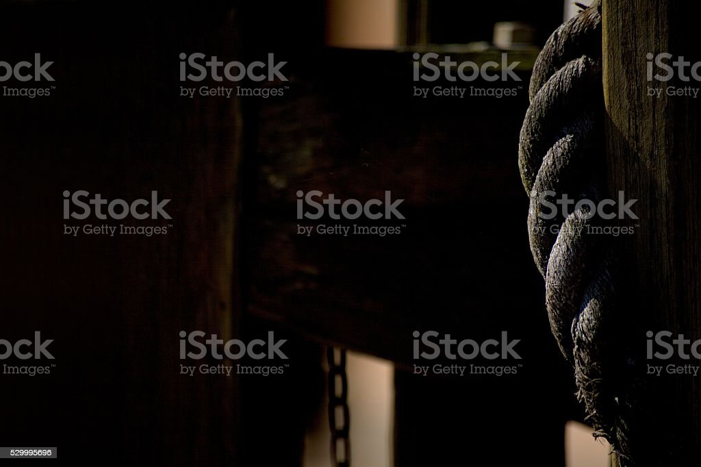 Wooden fence and rope on black background stock photo