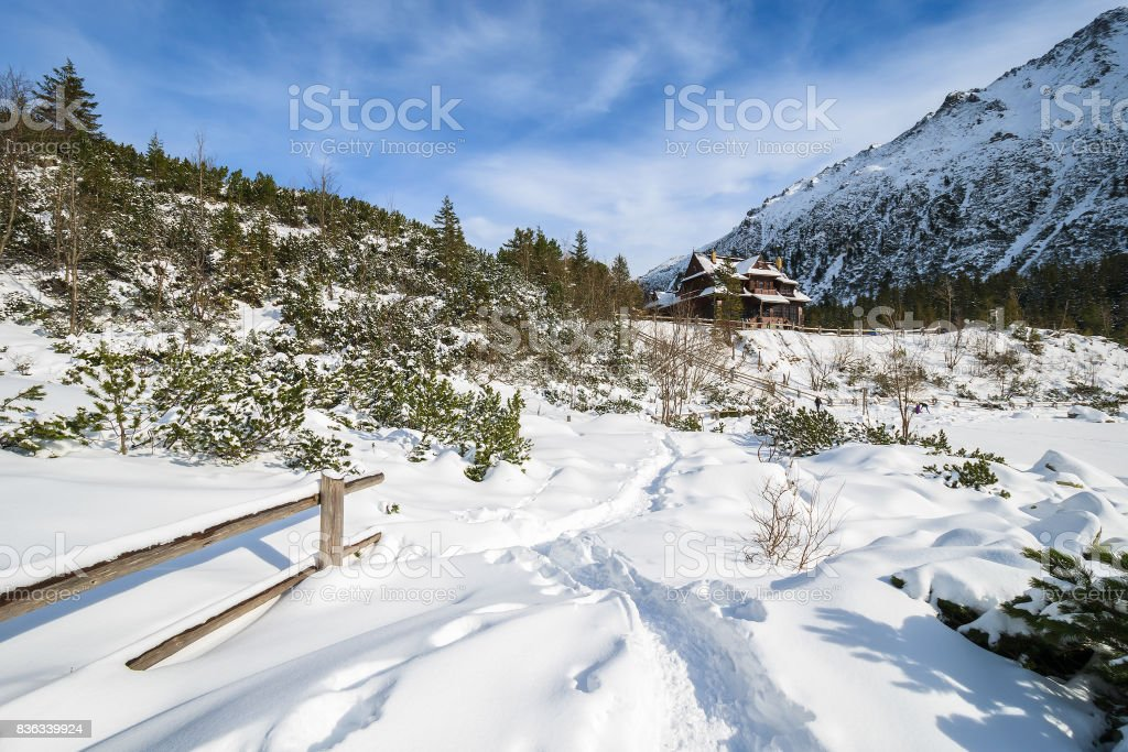 Wooden fence and snow path to Morskie Oko refuge in winter, High Tatra Mountains, Poland stock photo
