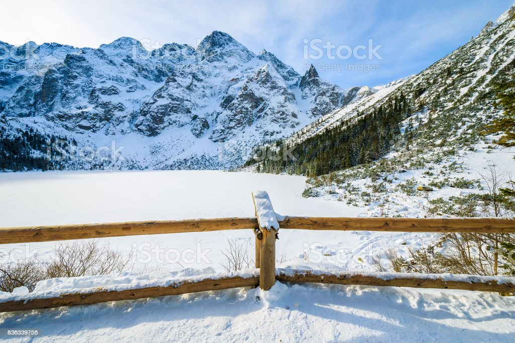 Wooden fence and view of frozen Morskie Oko lake in winter, Tatra Mountains, Poland stock photo