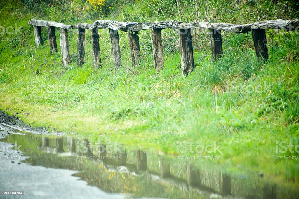 Wooden fence at roadside, puddle reflection. stock photo