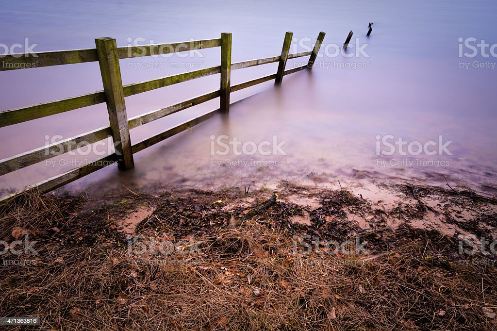Wooden Fence Flooded By Deep colorful Water. stock photo
