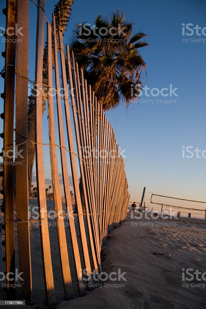 Wooden Fence In The Sand At Sunset royalty-free stock photo