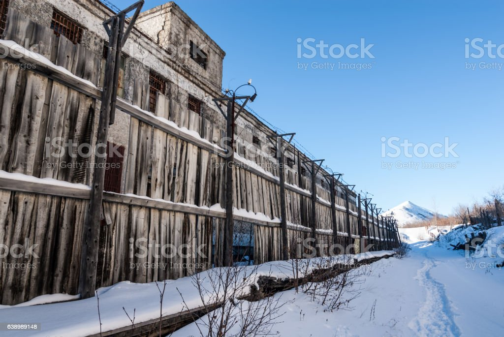 Wooden fence of abandoned prison stock photo