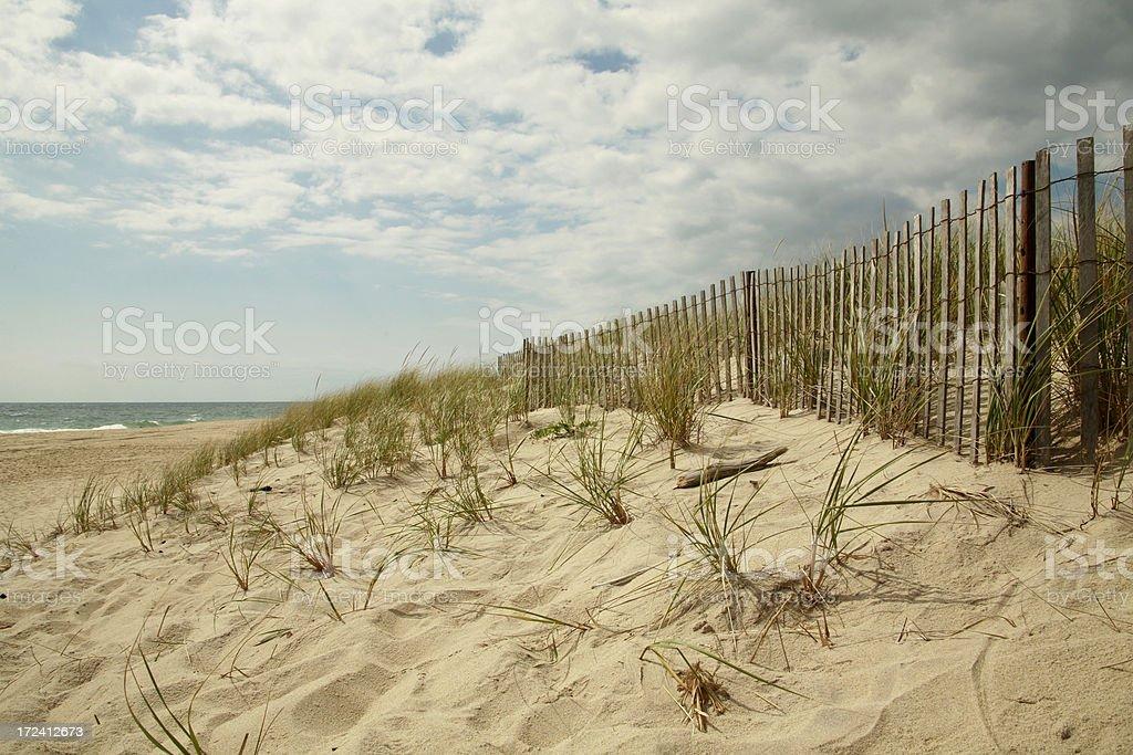 Wooden fence running along dunes stock photo
