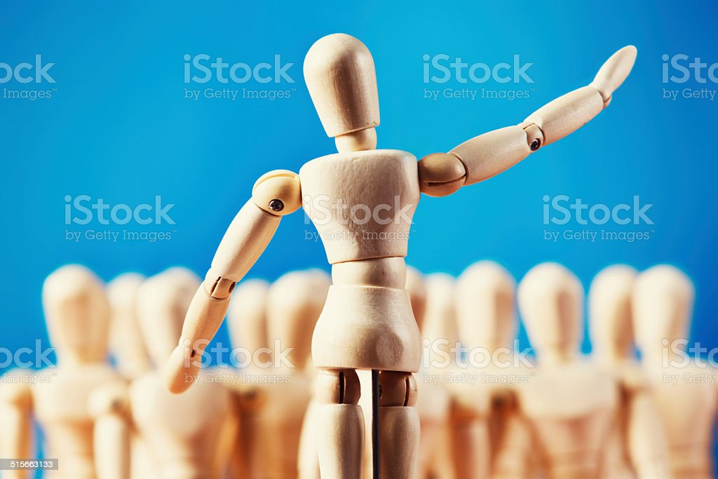 Wooden figure addressing puppet audience stock photo