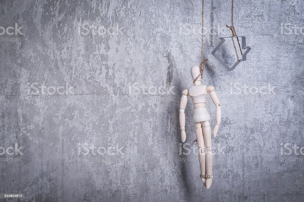 Wooden figure of human and house in a hangmans loop stock photo