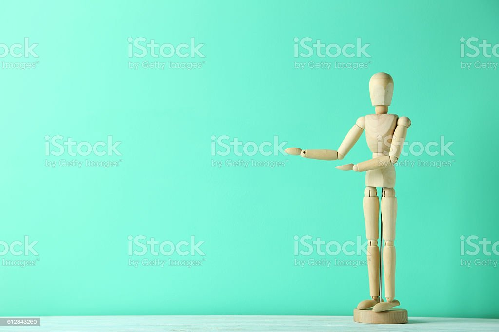 Wooden figure on a green wooden table stock photo