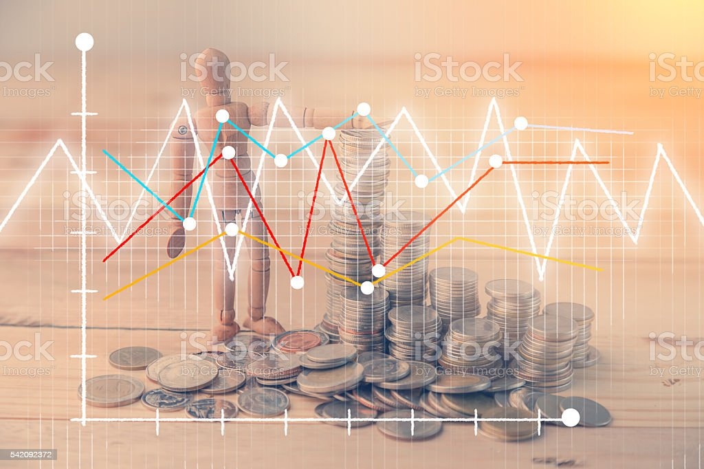 wooden figure with coin tower background with business graph ana stock photo