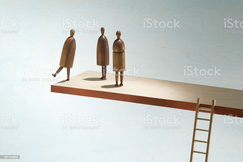 Wooden figures on the edge of a wooden shelf with ladder royalty-free stock photo