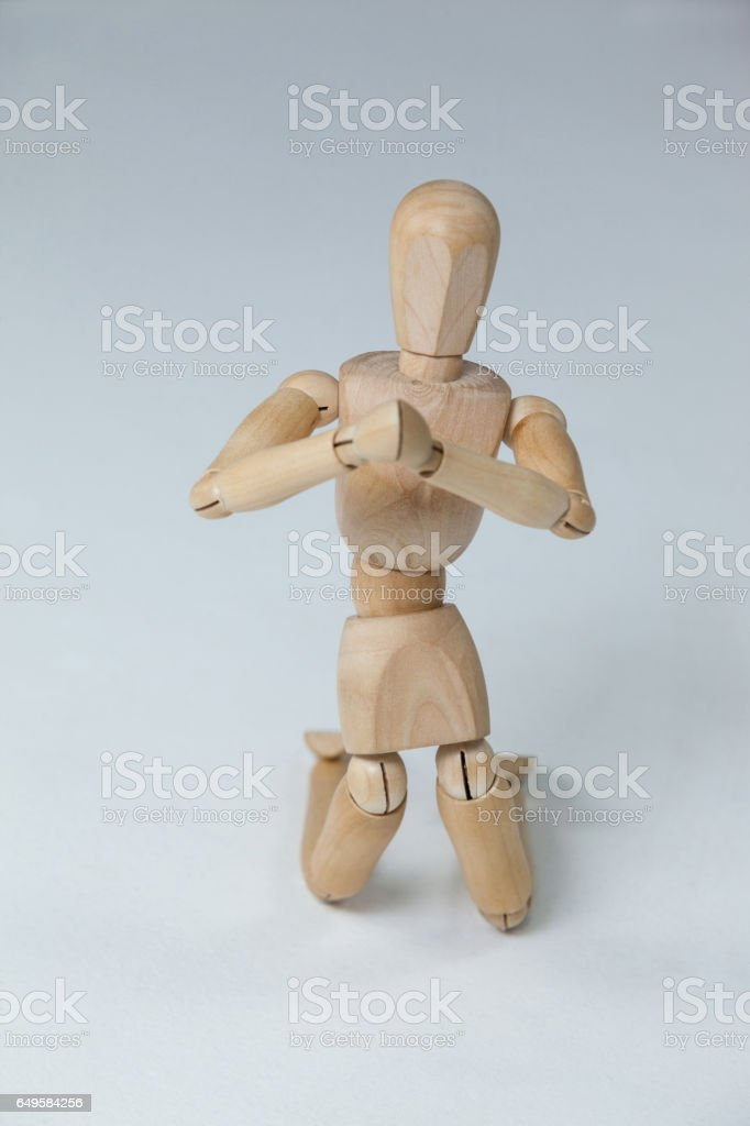Wooden figurine kneeling with both hands joined royalty-free stock photo
