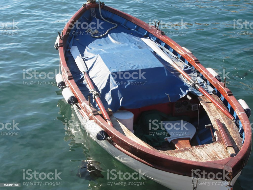 Wooden fishing boat anchored in a village port stock photo