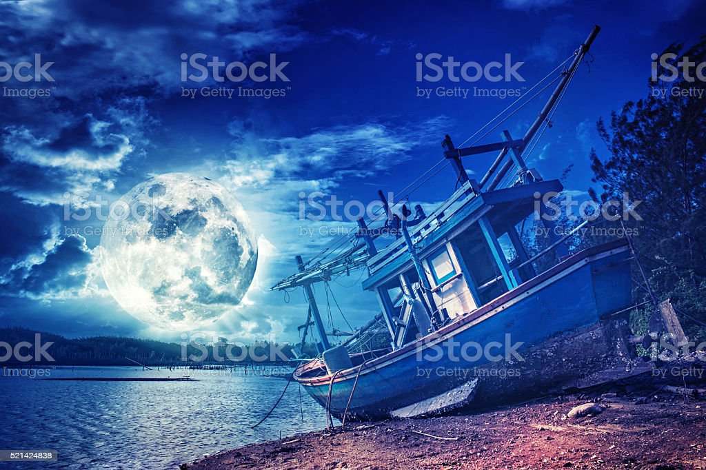 wooden fishing boat on a beach under a full moon stock photo