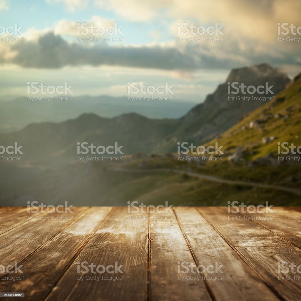 Wooden floor and defocused mountain valley on background. stock photo