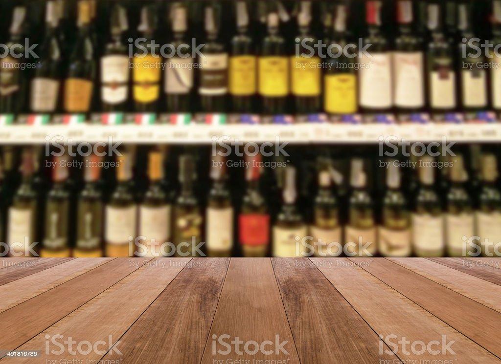 wooden floor and wine Liquor bottle on shelf blurred background stock photo