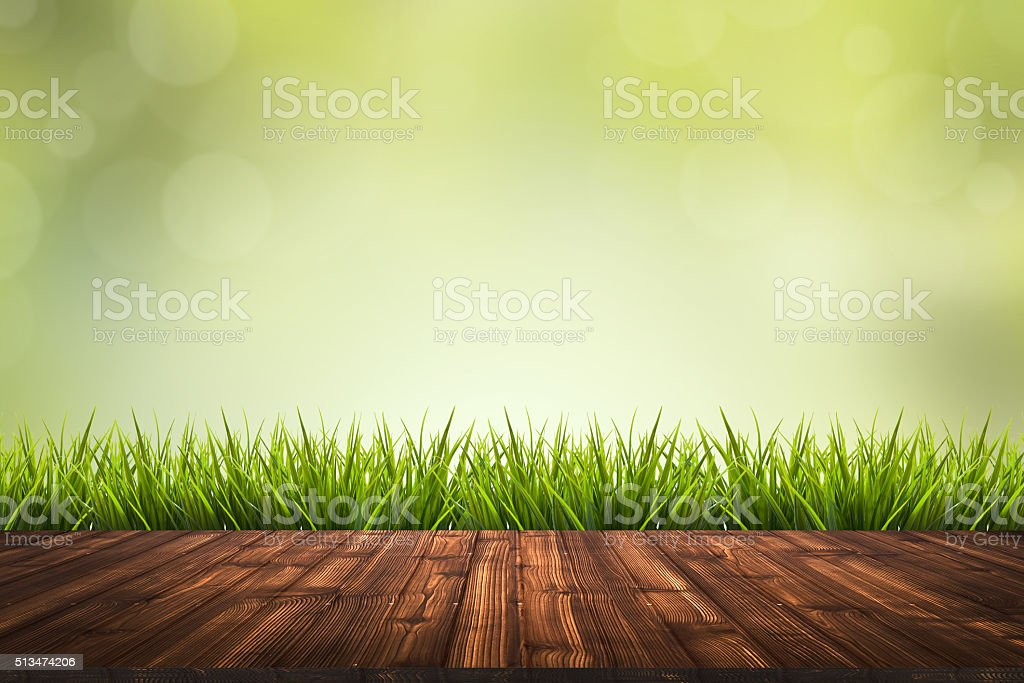 Wooden floor, grass and green blurred background stock photo