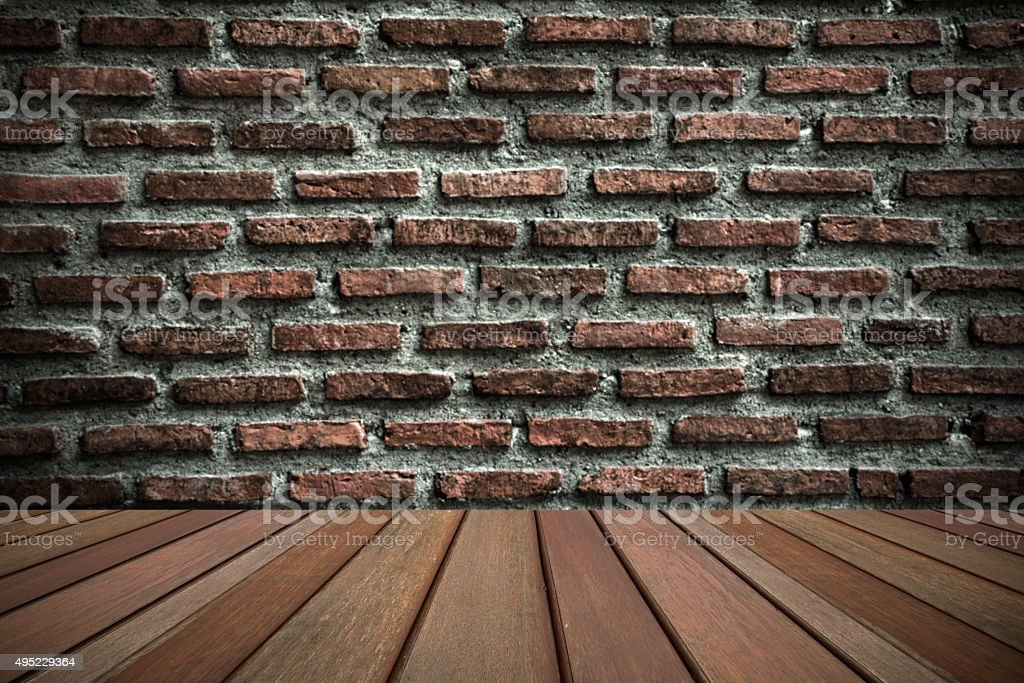 Wooden floor top on blurry brick wall in background. royalty-free stock photo