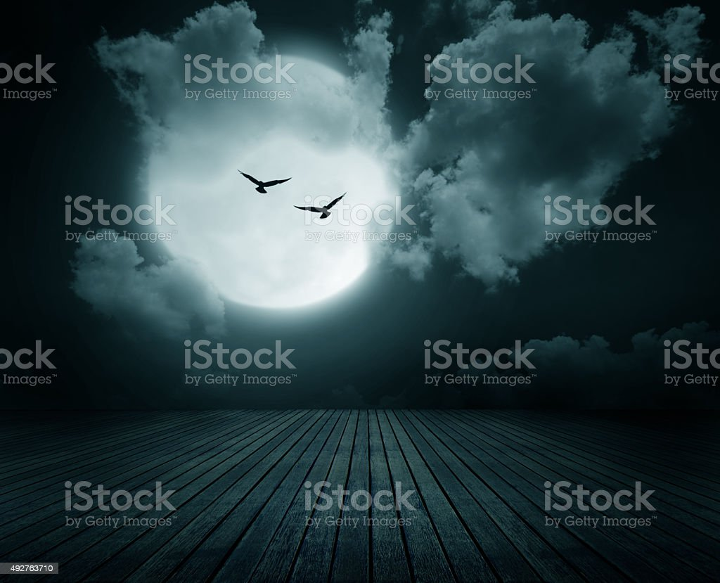 Wooden floor with branch and blurred full moon stock photo