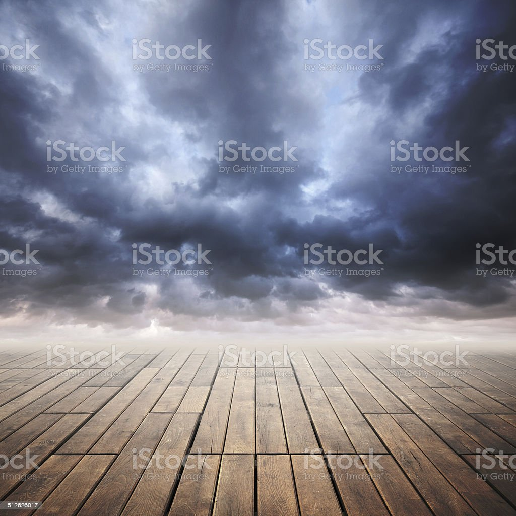 Wooden floor with perspective and stormy cloudy sky stock photo