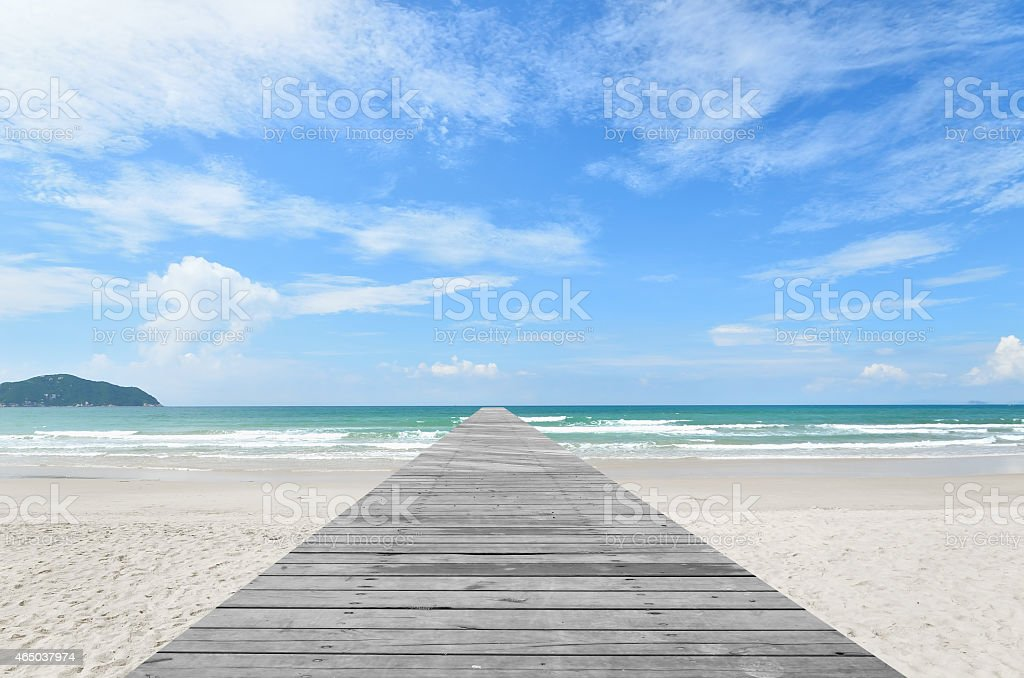 Wooden footbridge into tropical sea stock photo