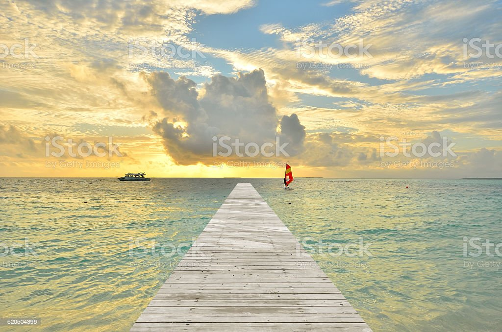 Wooden footbridge leading to the tropical sea with sunset stock photo
