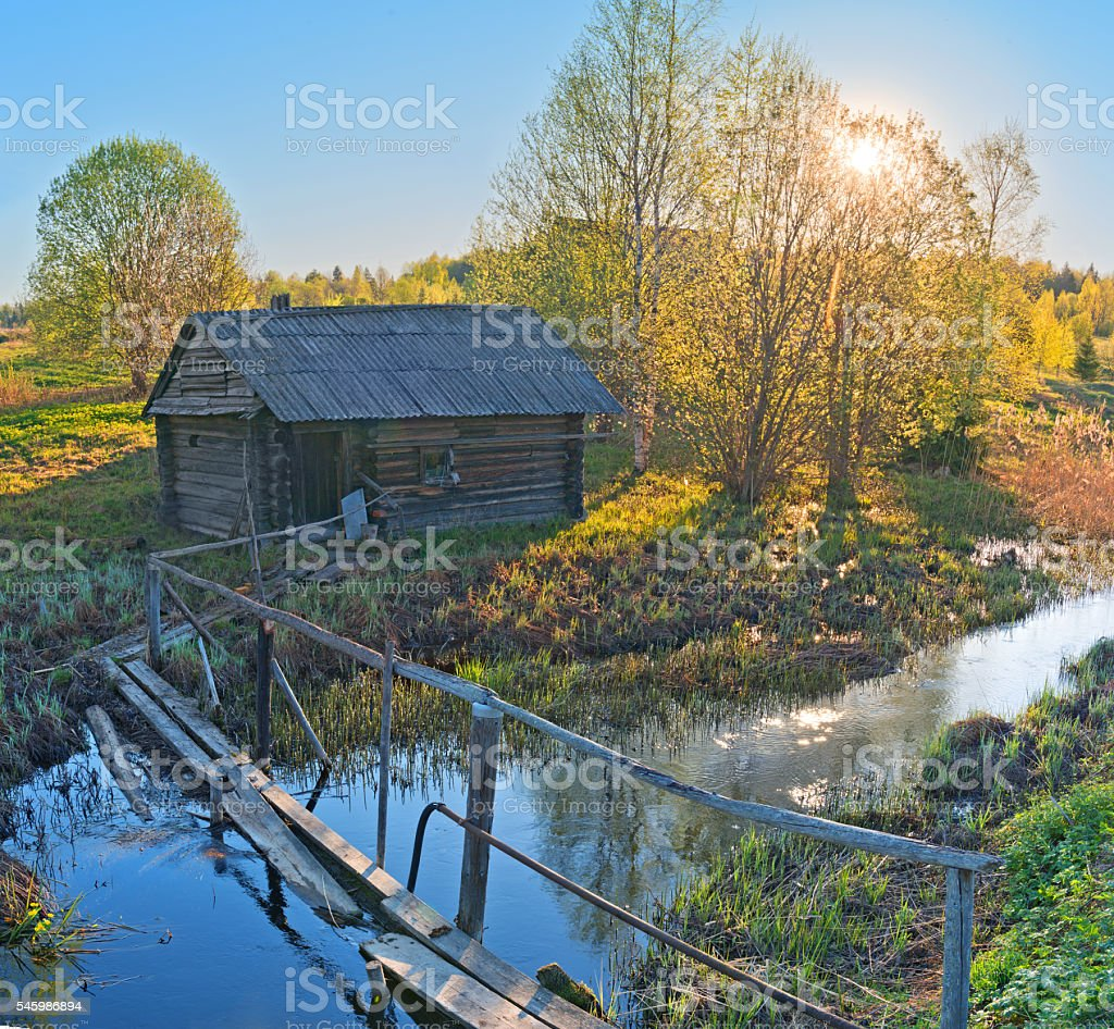 Wooden footbridge over creek leading to little house. stock photo