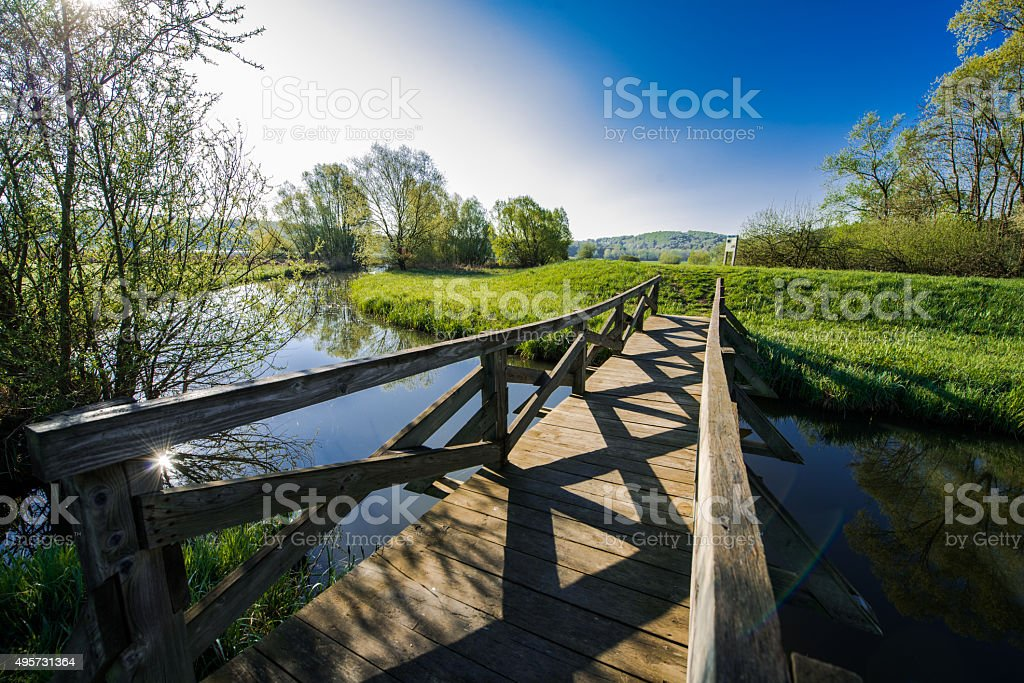 Wooden footbridge over small river stock photo