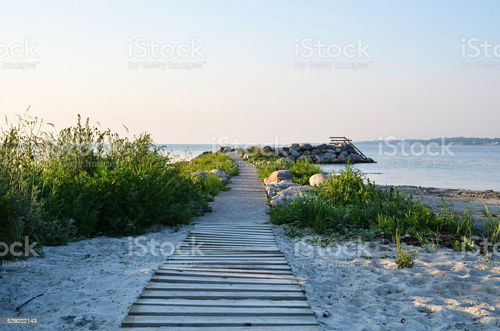 Wooden footpath at the beach stock photo