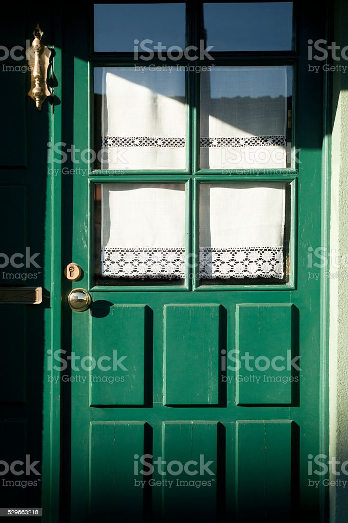 Wooden front door at dusk, beautiful knocker, embroidery. stock photo