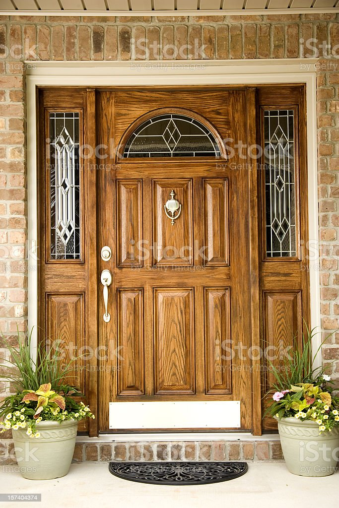 Wooden front door of a brick house with two flower pots stock photo