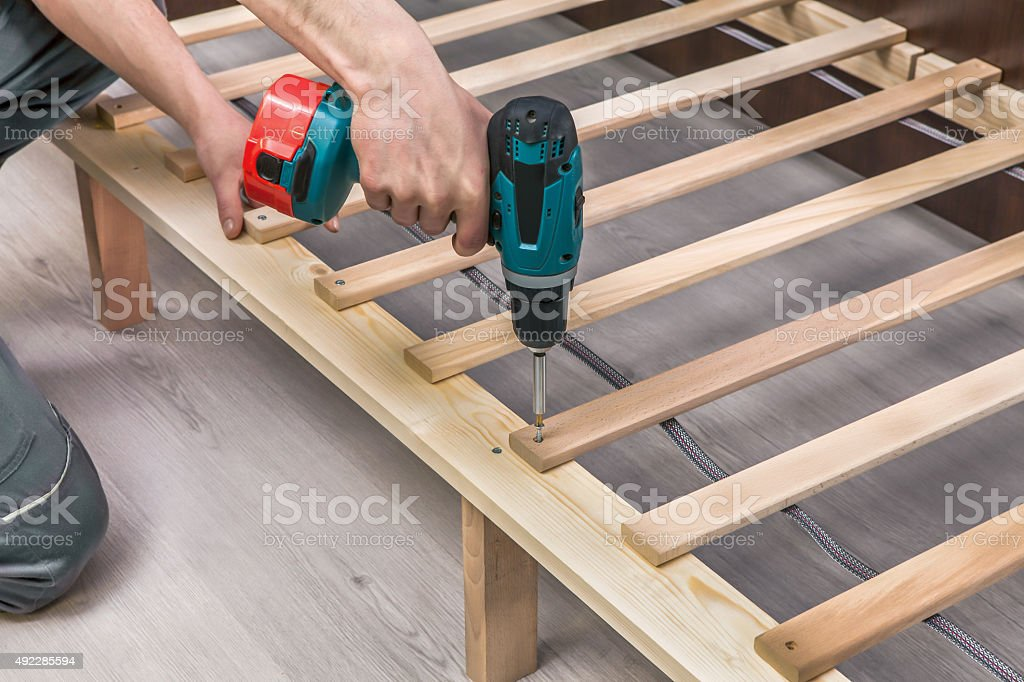 Wooden furniture assembling- woodworker screwing screws using a cordless stock photo