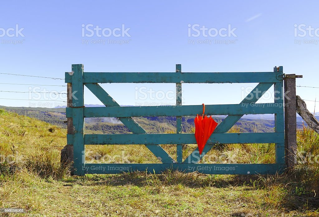 Wooden gate and red umbrella. stock photo