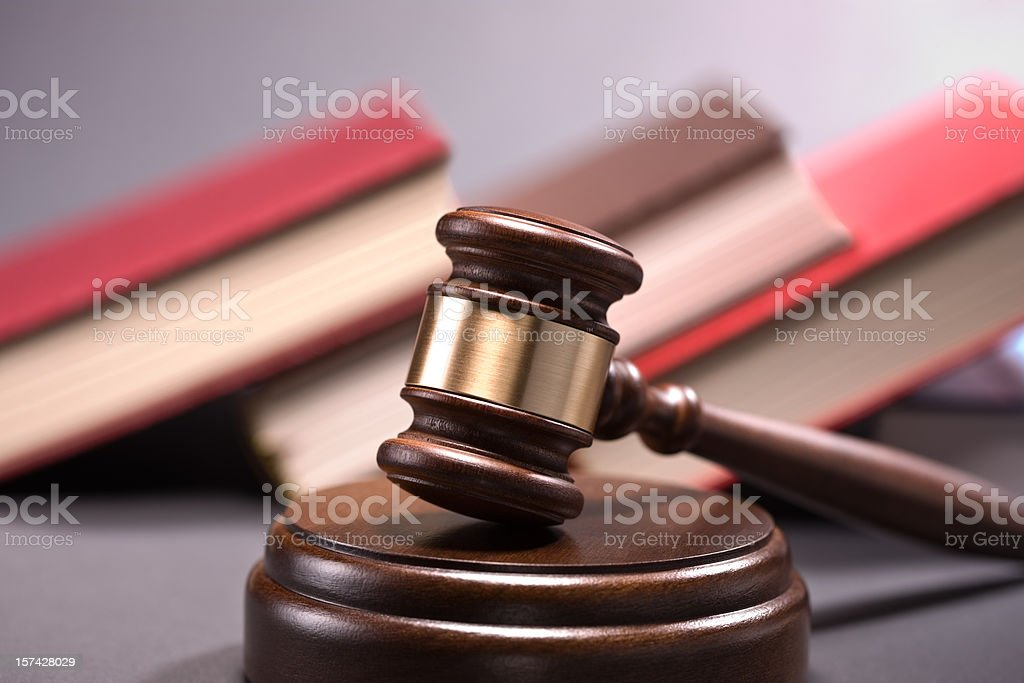 Wooden gavel and law books in the row on background royalty-free stock photo