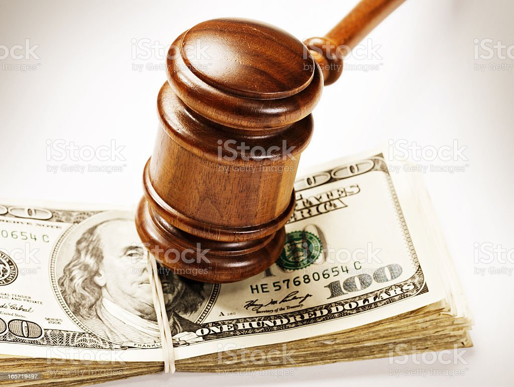 Wooden gavel bangs down on bundle of US dollars royalty-free stock photo