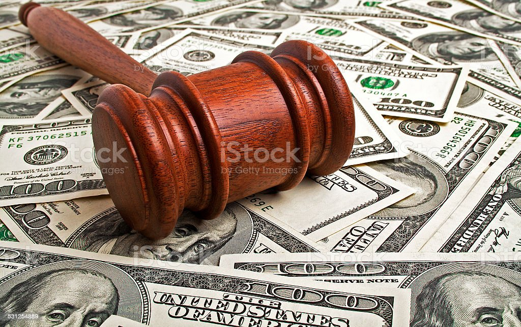 Wooden gavel laying on American dollars stock photo