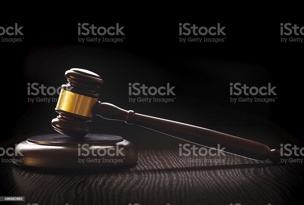 Wooden gavel on a textured dark wood surface stock photo