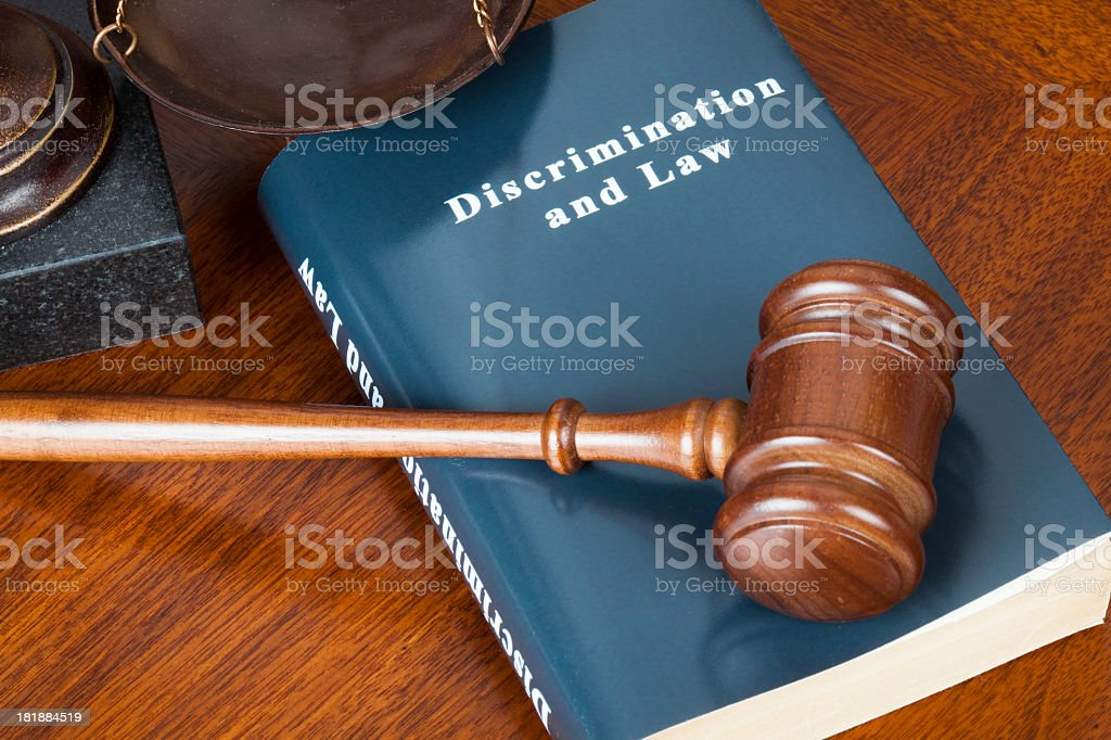 Wooden gavel placed on top of discrimination law book stock photo