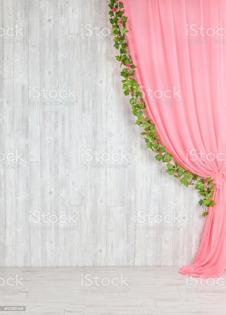Wooden gray wall with a pink curtain and flowers. stock photo