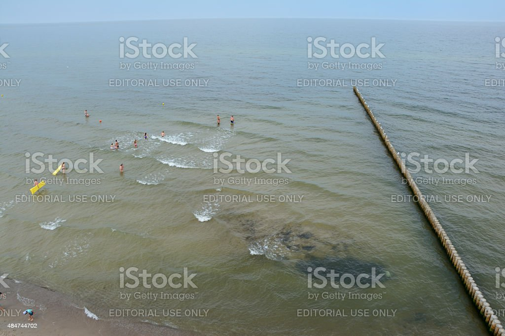 Wooden groyne and people bathing in the sea. stock photo