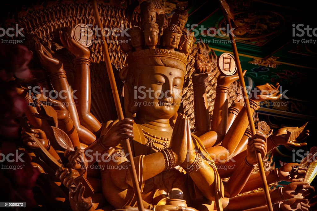 Wooden Guanyin buddha statue with thousand hands in Thailand stock photo