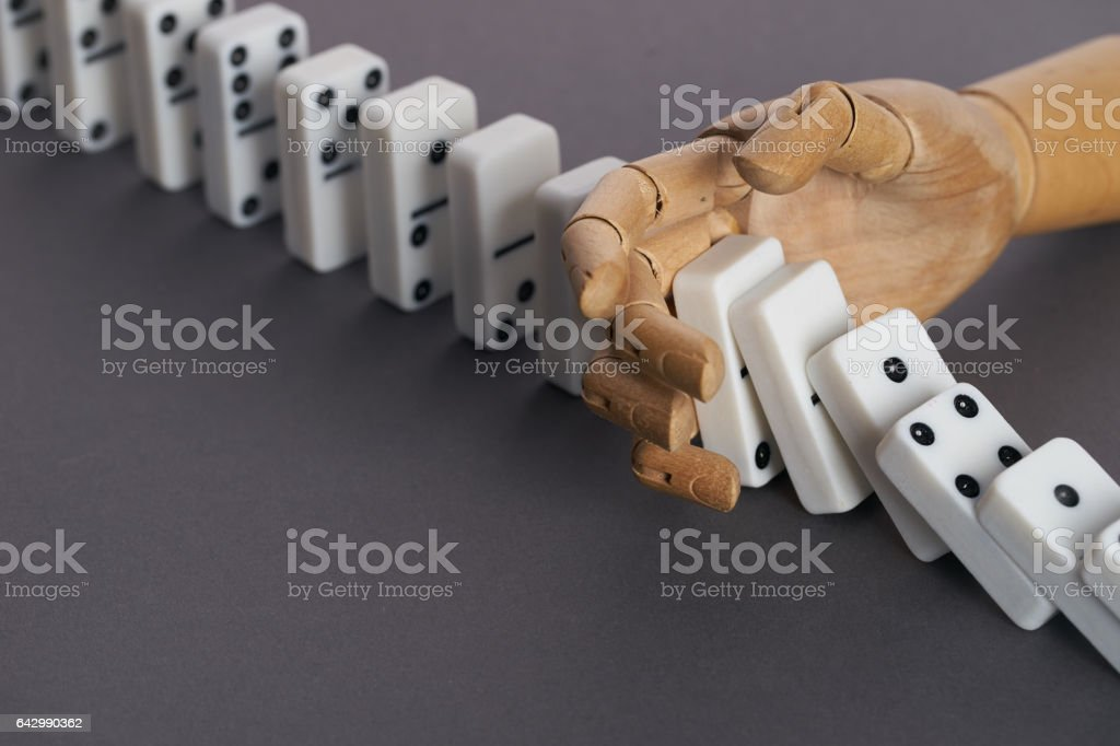 Wooden hand trying to stop toppling dominoes stock photo