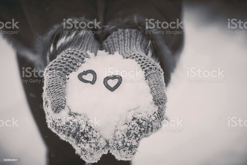 wooden hearst in the hands with snow stock photo
