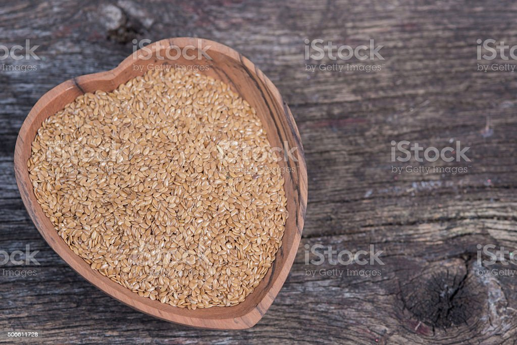 Wooden heart dish with flax seeds stock photo