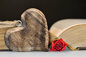 Wooden heart, dry rose and old book