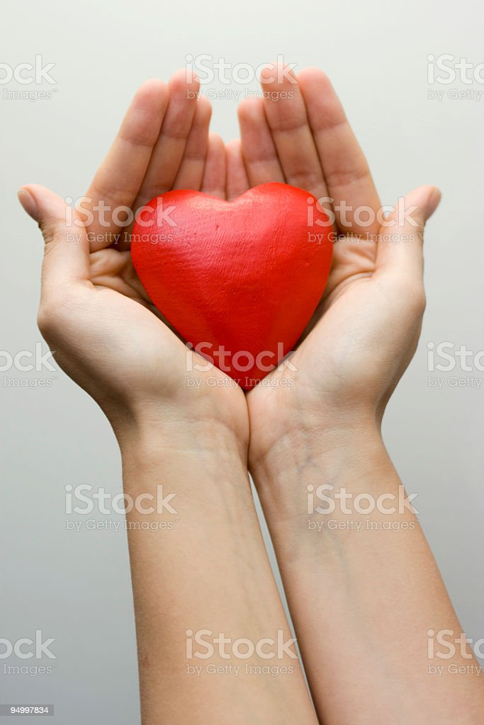 Wooden heart in palms royalty-free stock photo
