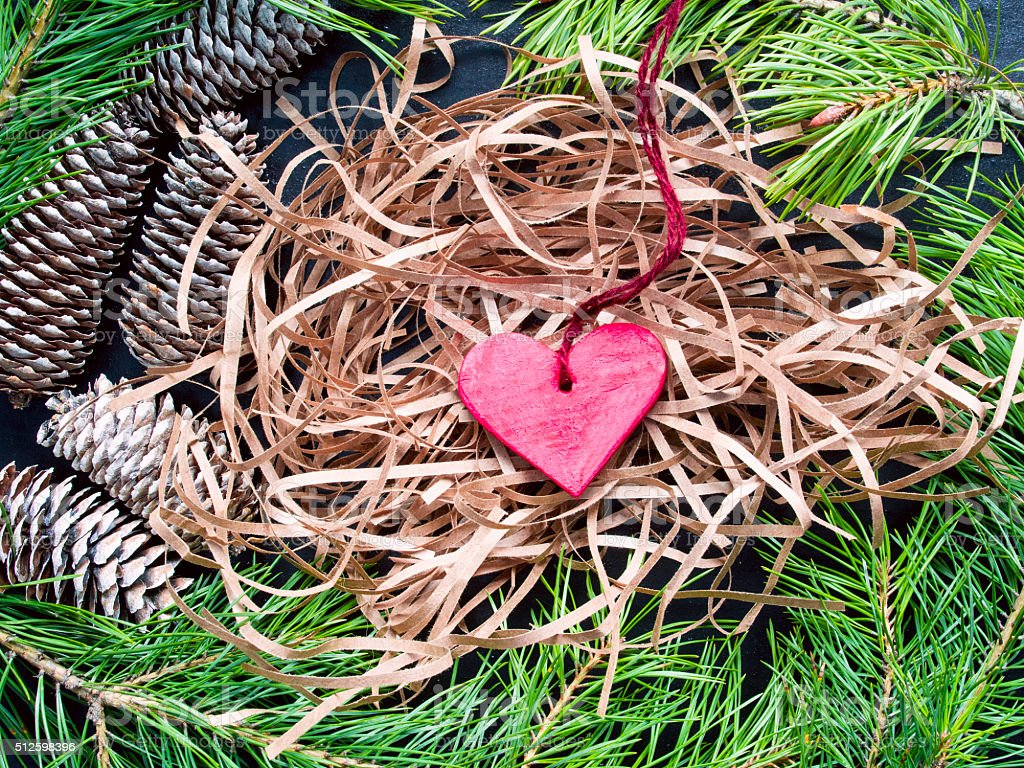 Wooden heart on a background tinsel, pine branches, cones stock photo