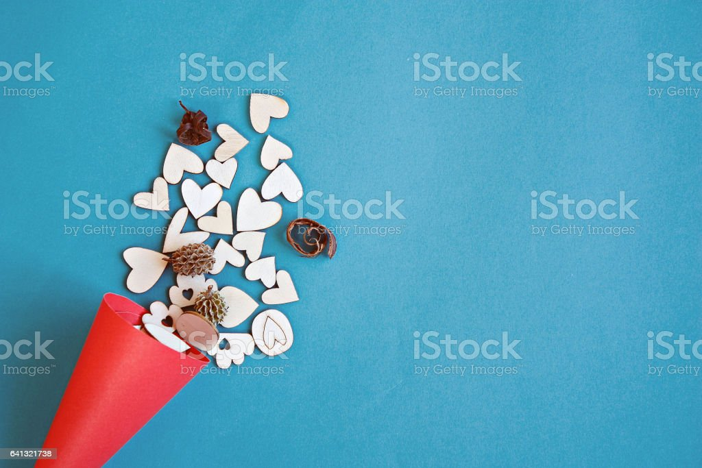 Wooden hearts in a red craft paper cornet on blue background stock photo